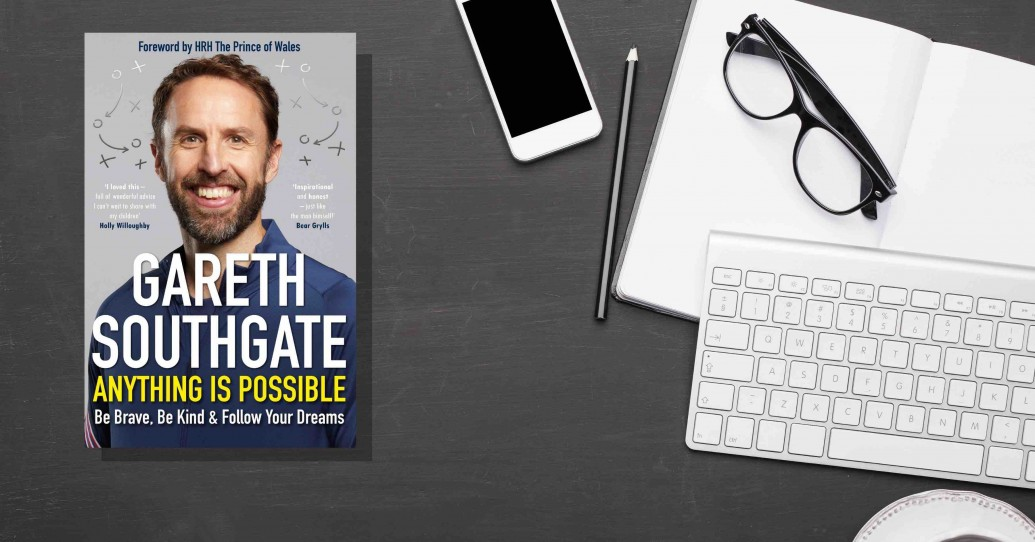 Photo of Gareth Southgate's book Anything is Possible with an iphone, keyboard and glasses on a desk.