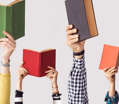 Hands holding up different books